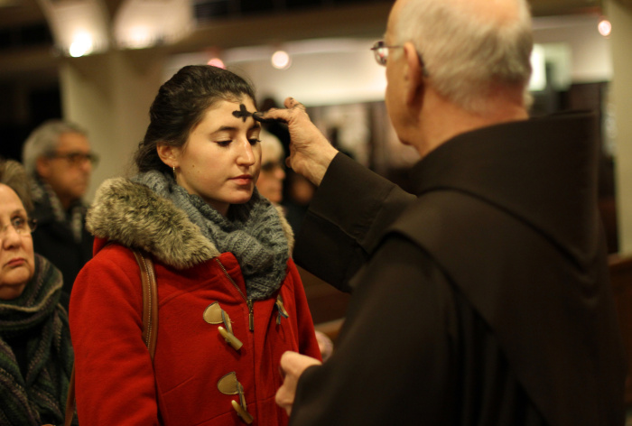 Woman recieves ashes from religious brother on Ash Wednesday at New York church