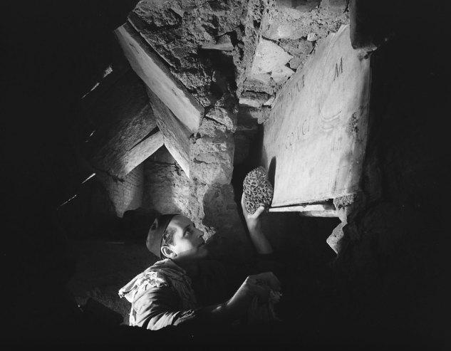 Рабочий очищает надпись во время раскопок под собором Св.Петра. Рим,1950 год.